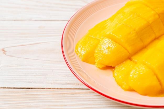 プレートにスライスした新鮮で黄金のマンゴー