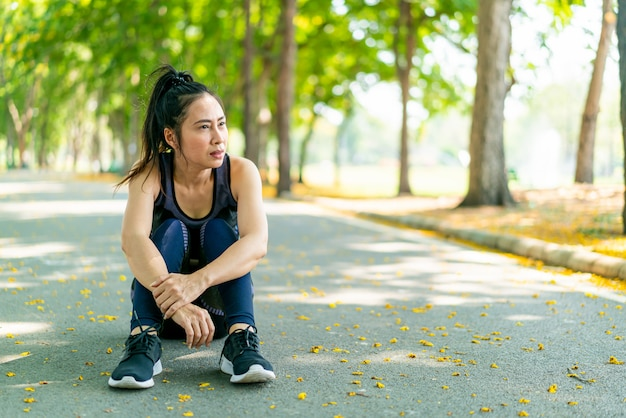 座っているアジアの女性と公園で運動後のスポーツウェアでリラックス