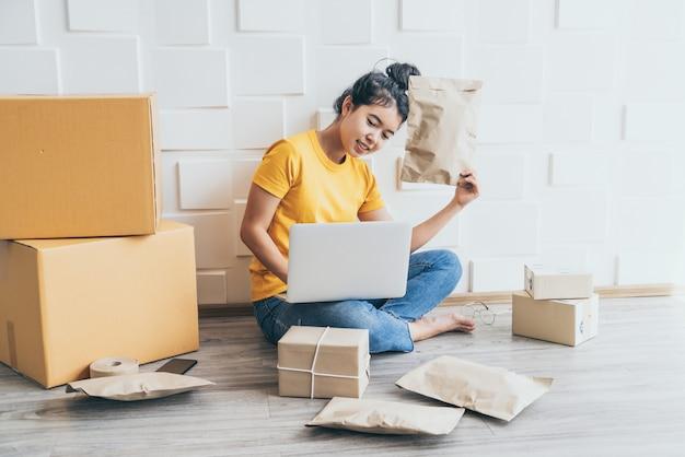若いアジアビジネスは、コンピューターを使用して所有者を起動します。およびパッケージの準備