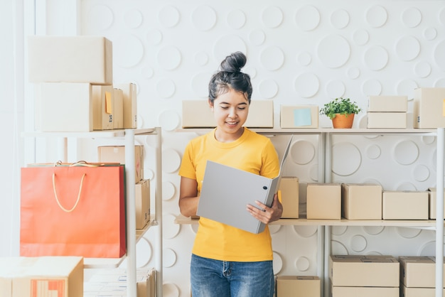 若いアジア女性が倉庫の在庫棚の商品をチェック