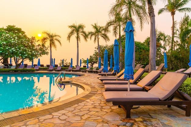 日没時にプールの周りに傘が付いたビーチチェアまたはプールベッド