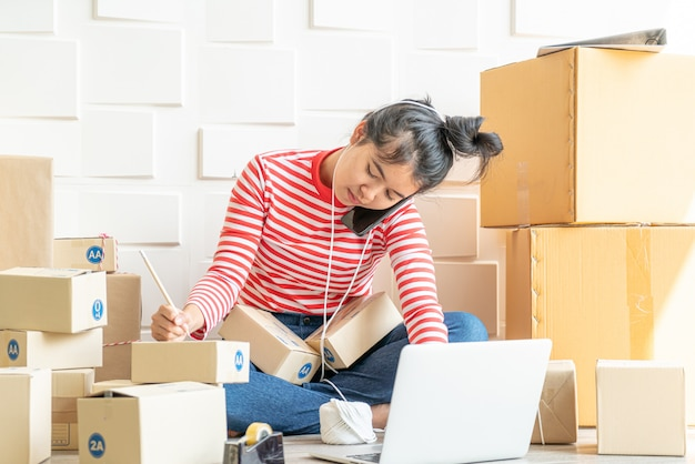 職場での梱包箱で自宅で働くアジアのビジネスオーナー