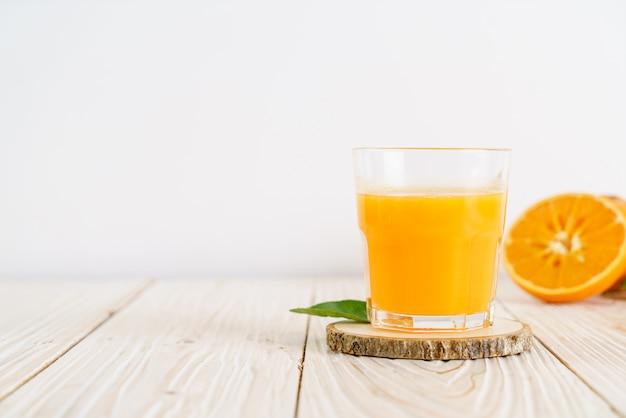 木のテーブルに新鮮なオレンジジュース