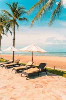 Красивый тропический пляж и море с зонтиком и стулом вокруг бассейна в отеле-курорте для путешествий и отдыха