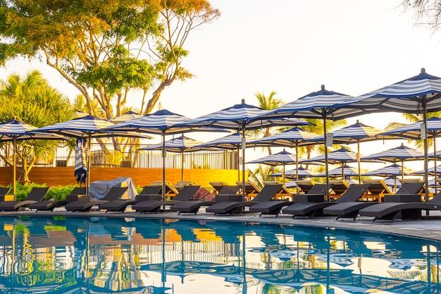 旅行休暇休暇の概念のためのホテルリゾートの屋外スイミングプールの周りの傘とプールベッド
