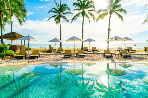 美しい豪華な傘とホテルとリゾートの屋外スイミングプールの周りの椅子青い空にココヤシの木と
