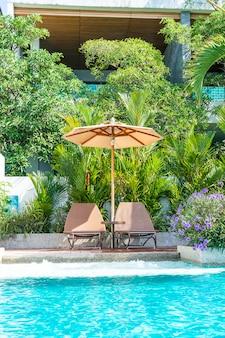 ホテルとリゾート-休暇の概念で美しい傘とプールの周りの椅子