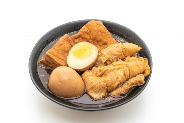 ブラウンソースまたは甘いグレービーソースの白い背景で隔離のゆで卵