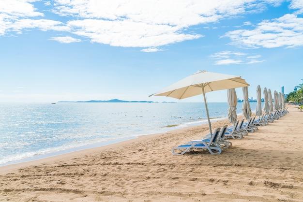 Открытый с зонтиком и стулом на прекрасном тропическом пляже и на море
