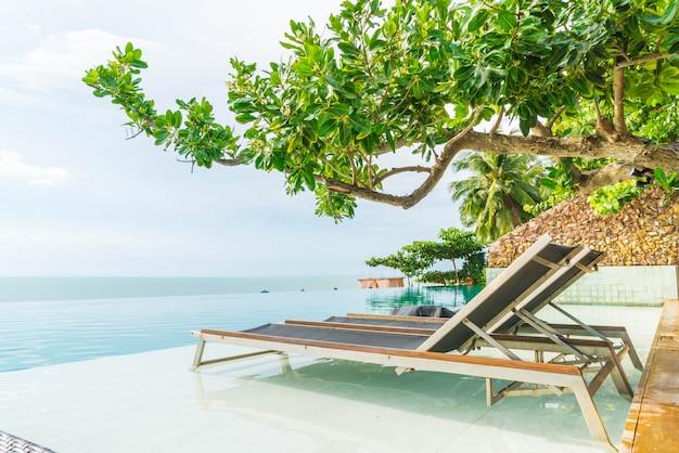 美しい高級傘とホテルやリゾートの屋外スイミングプールの周りの椅子