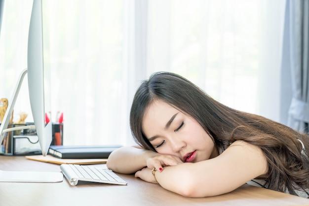 Ленивая азиатская женщина спит в офисе
