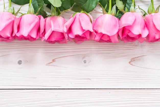 木製の背景の上に花瓶にピンクのバラ