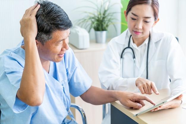 Азиатский старший пациент, имеющий консультацию с доктором