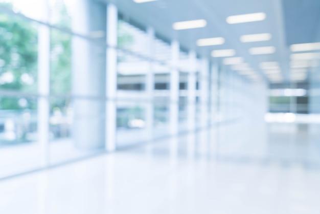 Размытый абстрактный фон интерьера, глядя на пустой офис лобби и входные двери и стеклянные занавески стены с рамой