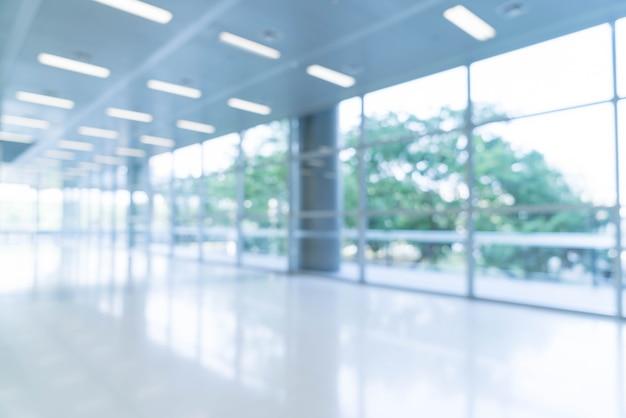 空のオフィスロビーと入り口のドアとフレーム付きのガラスカーテンウォールに向かって見て、ぼんやりとした抽象的な背景のインテリアの眺め