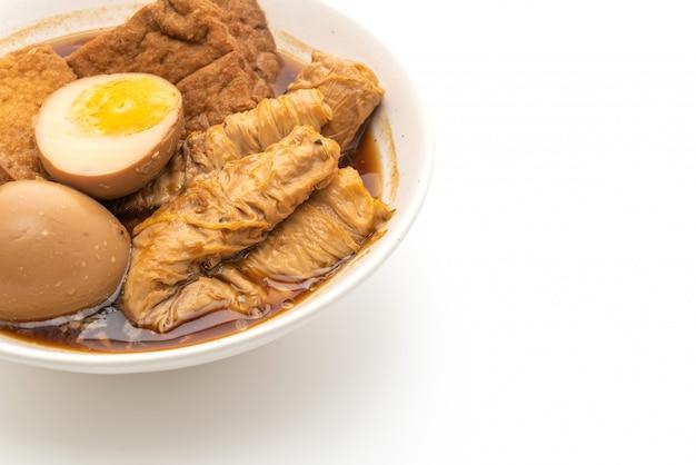 Яйцо вкрутую в коричневом соусе или сладком соусе на белом фоне