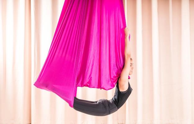 アジアの女性のフライのヨガの要素を持つフィットネスルームでトレーニング