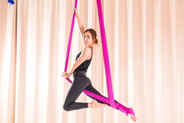 Азиатская тренировка женщины в спортзале с элементами йоги мухы