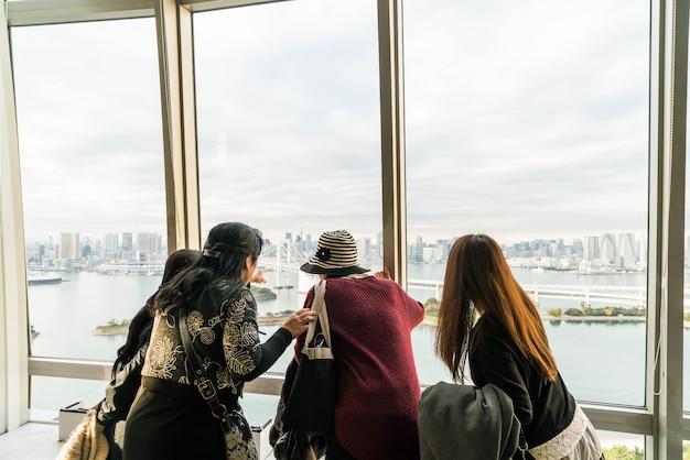 Толпа туристов и местных жителей наслаждается видом токийского залива из одайбы в пасмурный осенний день.
