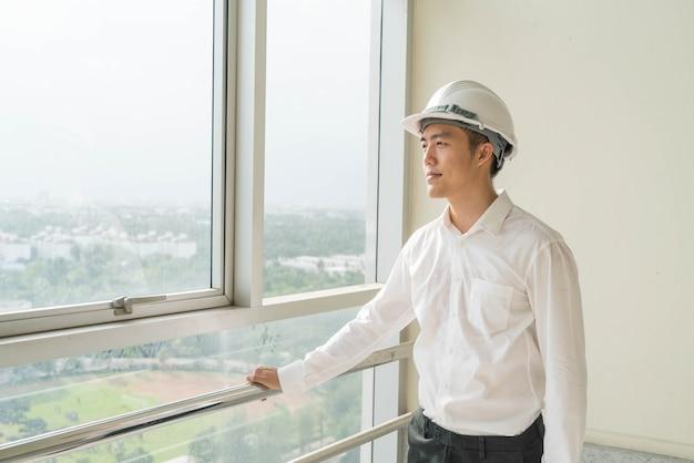 白い安全ハードヘルメットを持つ若いアジアエンジニア