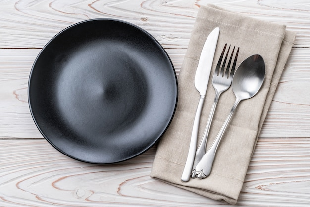 Пустая тарелка, ложка, вилка и нож
