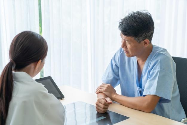アジアの先輩患者のオフィスで医者と相談