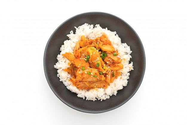 白い背景で隔離のご飯にキムチと豚肉の炒め物をかき混ぜる