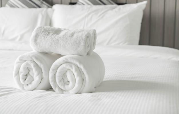 寝室のインテリアのベッドの装飾の上に白いタオル