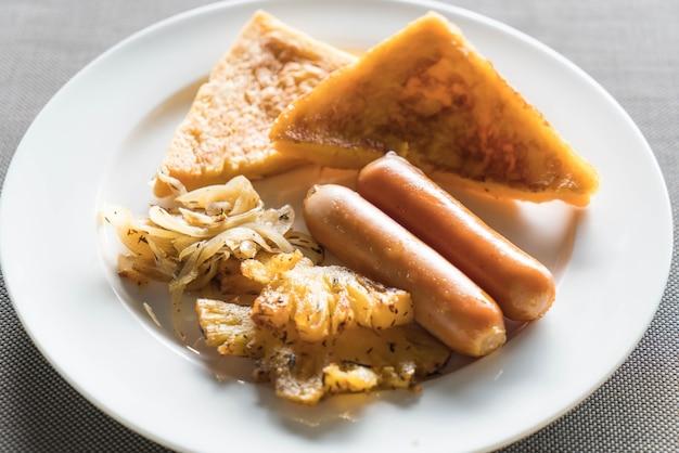 Завтрак с жареными ананасами, колбасами и тостами