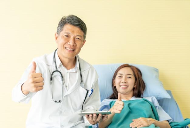 病院のベッドの上に座って、女性患者と議論するアジアの先輩医師