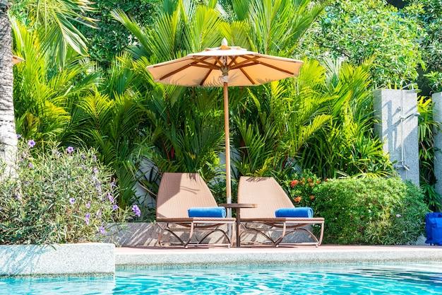 美しい傘とホテルとリゾート-休暇の概念のスイミングプールの周りの椅子