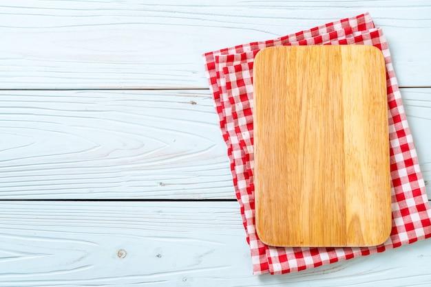 青い木製の背景、上面にキッチン布で空の切断木の板