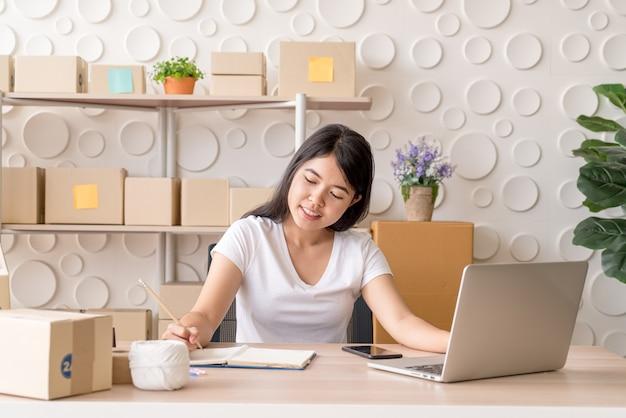 若いアジア女性は、職場でデジタルタブレットを使用して中小企業の所有者を起動します。