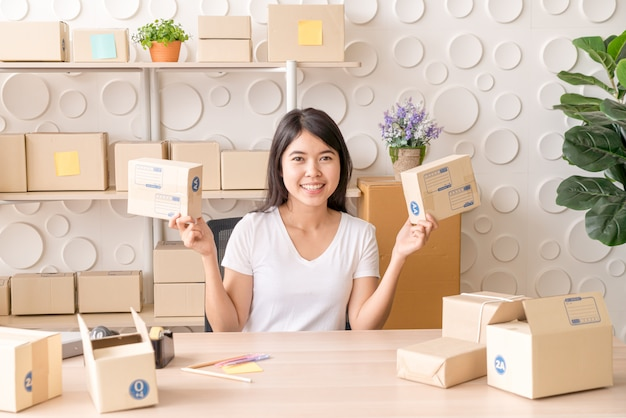 Владелец бизнеса азиатских женщин, работающих на дому с упаковочной коробки на рабочем месте