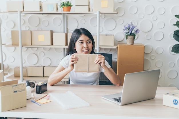 職場の梱包箱で自宅で働くアジアの女性ビジネスオーナー