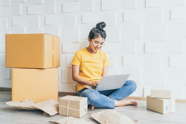 若いアジアのビジネスは、電子メールまたはウェブサイトから顧客の注文を確認し、パッケージを準備するためにコンピューターを使用してオンライン販売者の所有者を開始します