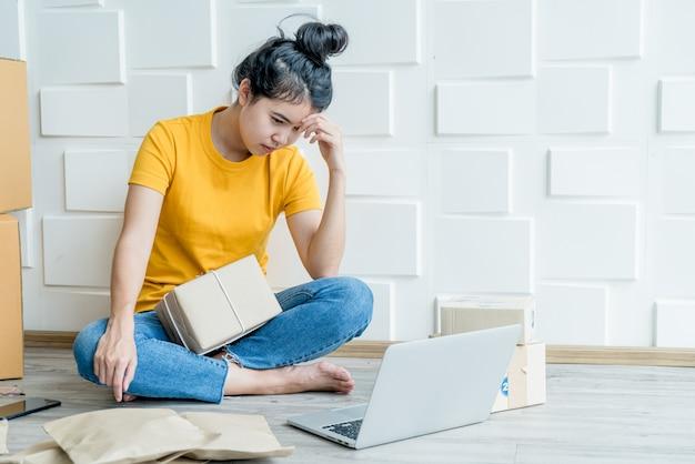 若いアジア女性のストレスを感じたり、彼女のラップトップの前で落ち込んで