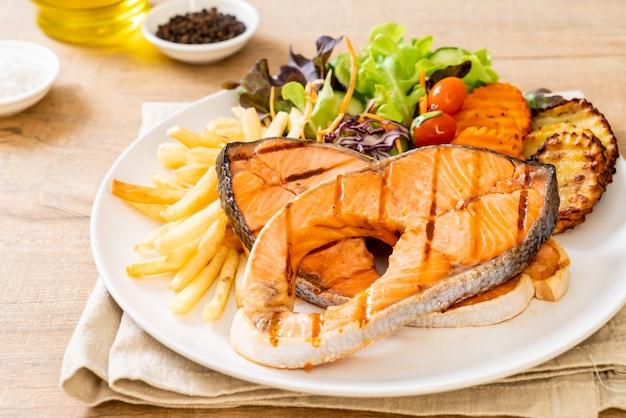 サーモンステーキフィレ肉のグリルと野菜とフライドポテト