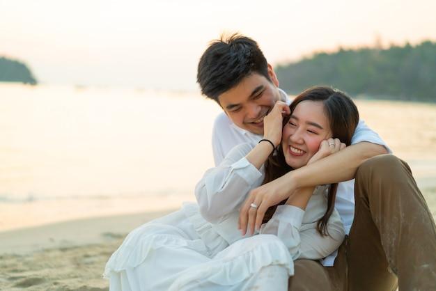 幸せなカップルが新婚旅行に行く夏の熱帯の砂浜に旅行します。