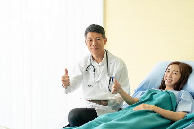 Азиатский старший доктор сидя на больничной койке и обсуждая с пациенткой