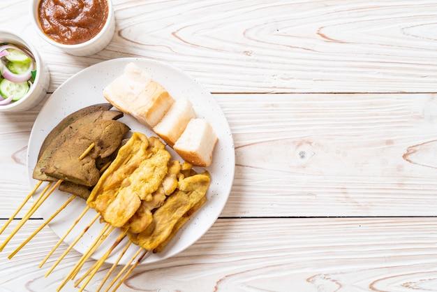 ピーナッツソースとキュウリのスライスと酢の玉ねぎのピクルスを添えたポークサテ