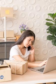 アジアの女性は、オフィスでラップトップと携帯電話でインターネットを使用しながら楽しんでいます