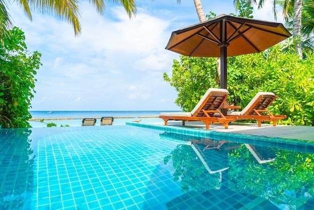 スイミングプールとモルディブの海の景色を望むビーチチェア