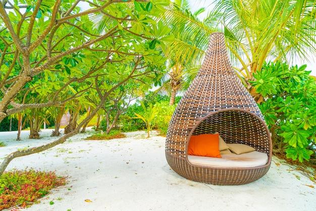 Подушка на диване украшает открытый внутренний дворик с видом на тропику и природу
