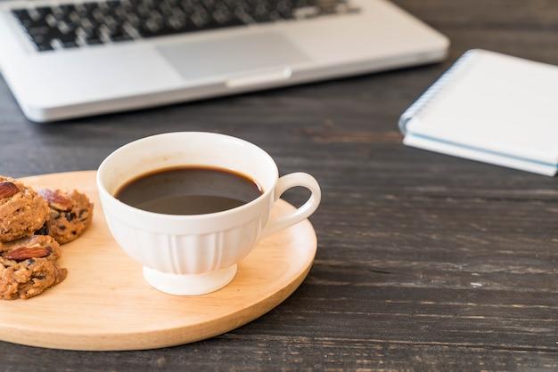 Черный кофе и печенье с ноутбуком и записная книжка