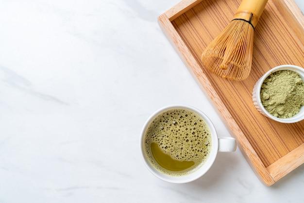 Чашка зеленого чая горячего матча с порошком зеленого чая и венчиком
