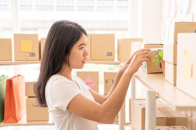 職場の梱包箱で自宅で働くアジアの女性ビジネス所有者