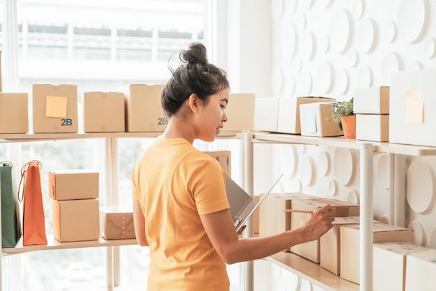 Молодая азиатка проверяет товар на складе полки на складе