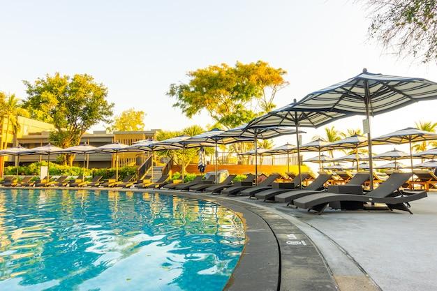 旅行休暇のためのホテルリゾートの屋外スイミングプールの周りの傘とプールベッド