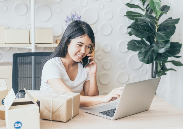 アジアの女性は、オフィスでノートパソコンと携帯電話でインターネットを使用しながら楽しんでいます